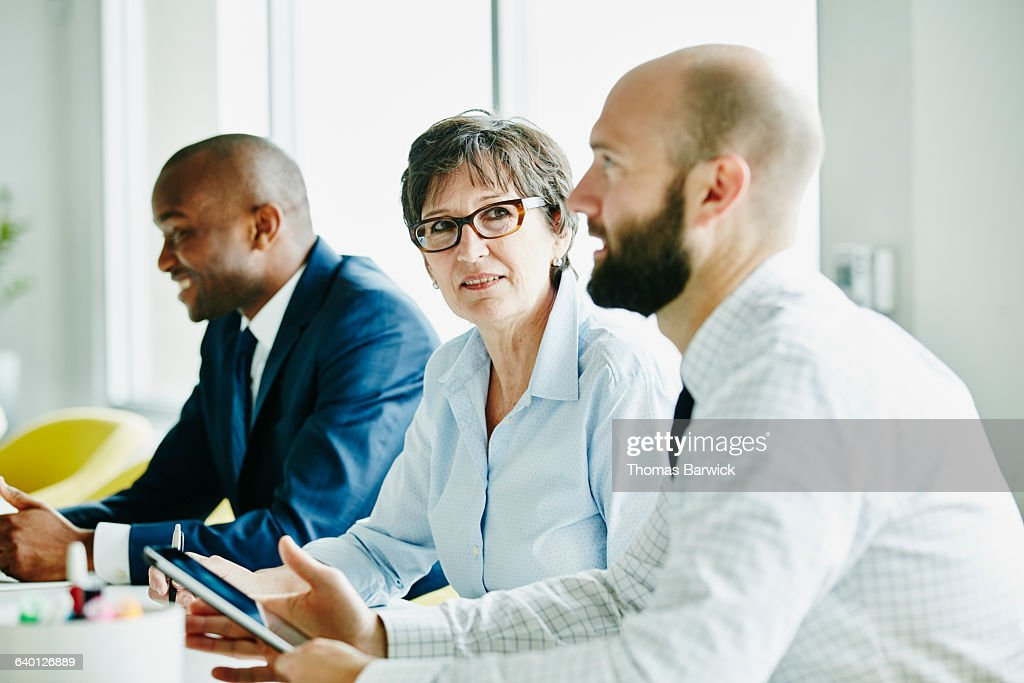 Mature businesswoman listening during meeting : Stock Photo