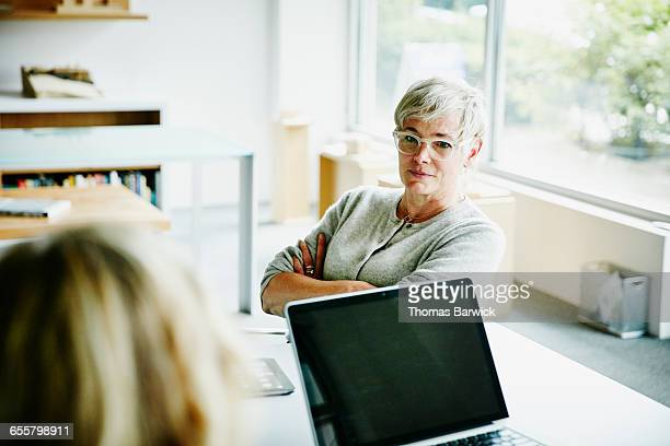 mature businesswoman listening during meeting - weibliche angestellte stock-fotos und bilder
