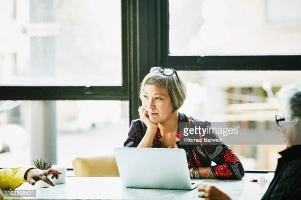 mature businesswoman listening during meeting with clients in office - 60 69 anos imagens e fotografias de stock