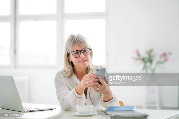 mature businesswoman looking at cell phone at desk - weibliche angestellte stock-fotos und bilder