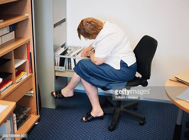 Mature businesswoman looking in files