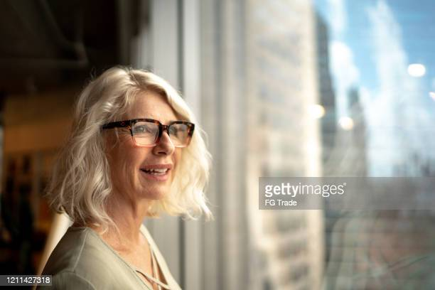 mature businesswoman looking out of window - gratitude stock pictures, royalty-free photos & images