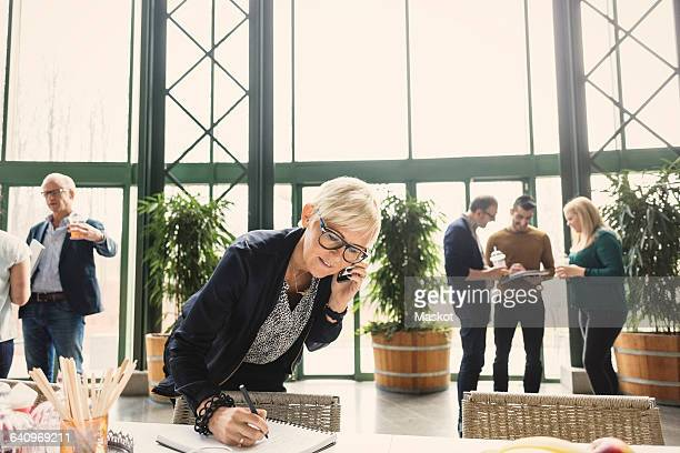 Mature businesswoman on call while writing in notepad with colleagues in background at office