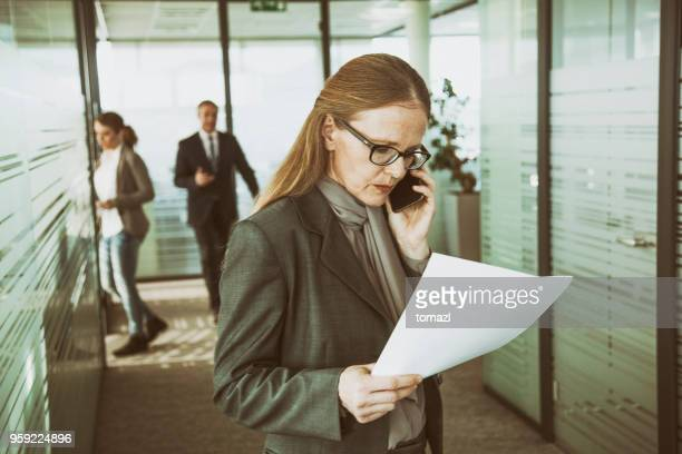 mature businesswoman on phone in an office coridor - surrey england stock pictures, royalty-free photos & images