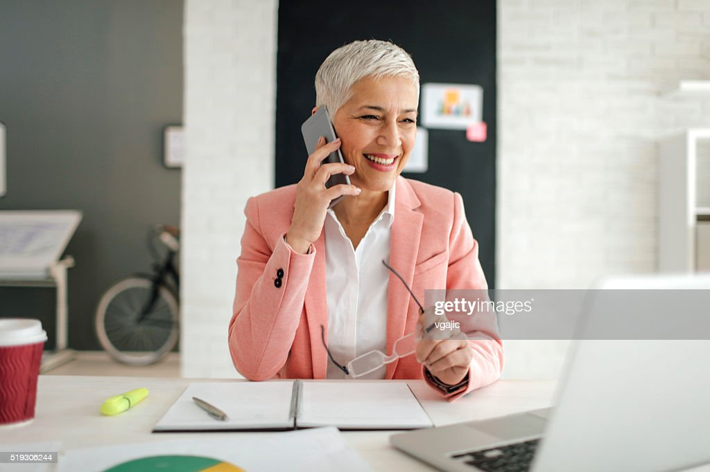 Mature Businesswoman On The Phone In Her Office. : Stock Photo