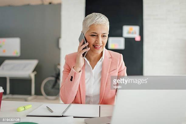 Maduro mujer de negocios hablando por teléfono en su oficina.