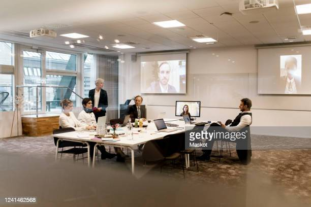 mature businesswoman planning strategy with team in board room during web conference meeting at office - video conference stock pictures, royalty-free photos & images