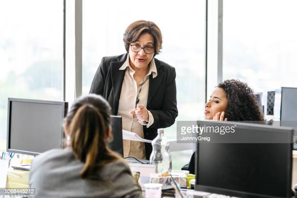 Mature businesswoman pointing at office worker and explaining