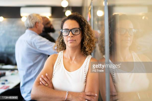 oudere zakenvrouw portret bij startup modern office - oprichter stockfoto's en -beelden