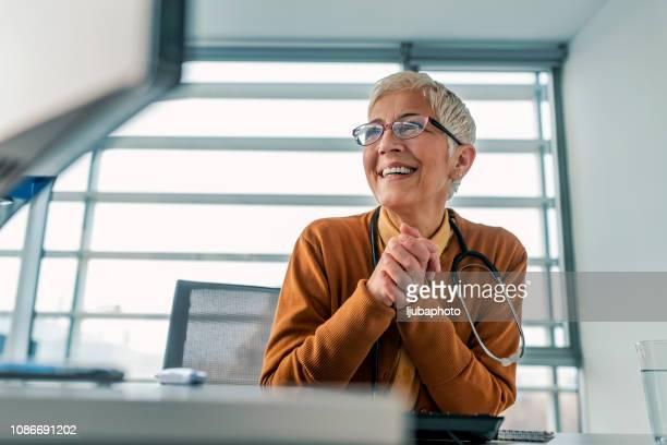 reife geschäftsfrau portrait in ihrem büro - hausarzt stock-fotos und bilder