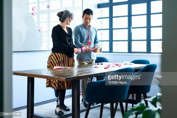 mature businesswoman problem solving with male colleague - thinking outside the box englische redewendung stock-fotos und bilder
