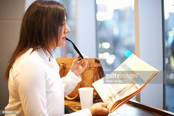 Mature businesswoman reading newspaper at city cafe, Tokyo, Japan