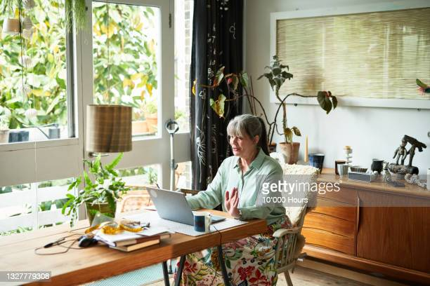 mature businesswoman remote working using laptop - working seniors stock pictures, royalty-free photos & images