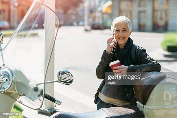 Mature Businesswoman Riding Scooter.
