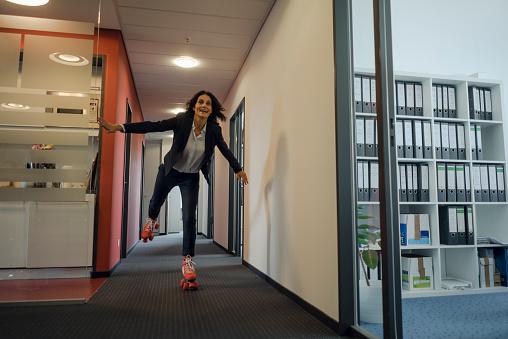Mature businesswoman rollerskating in office corridor - gettyimageskorea