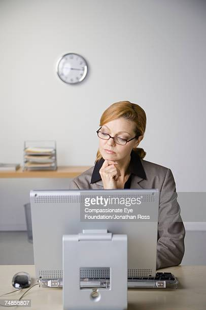 mature businesswoman sitting at desk in office, using computer - compassionate eye foundation stock pictures, royalty-free photos & images