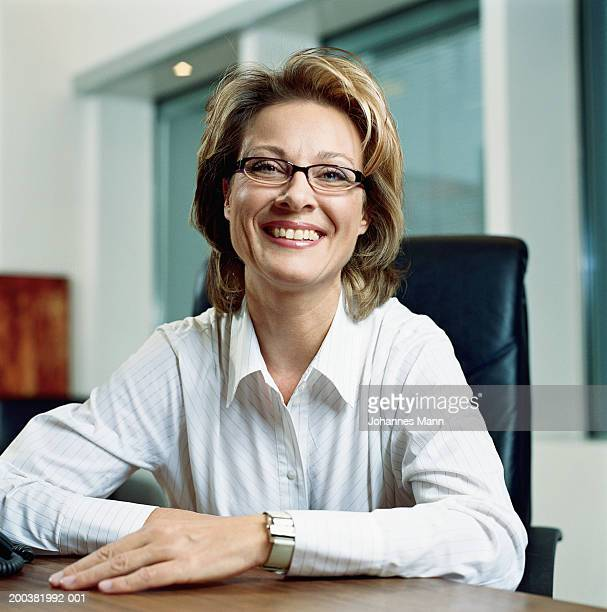 mature businesswoman sitting at desk, smiling, portrait - mid length hair stock pictures, royalty-free photos & images