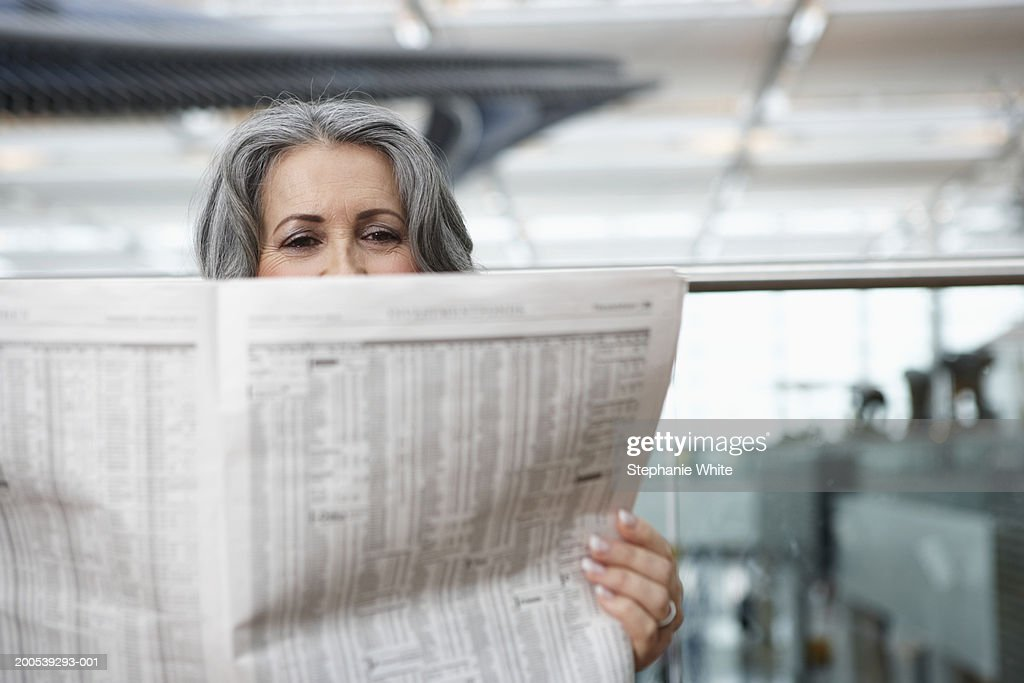 Mature businesswoman sitting in airport reading newspaper : Foto de stock