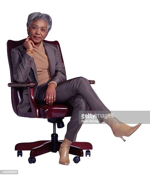 mature businesswoman sitting in office chair - businesswear stock pictures, royalty-free photos & images