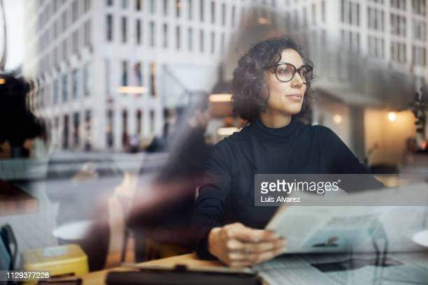 mature businesswoman sitting inside at cafe with newspaper - publication stock pictures, royalty-free photos & images