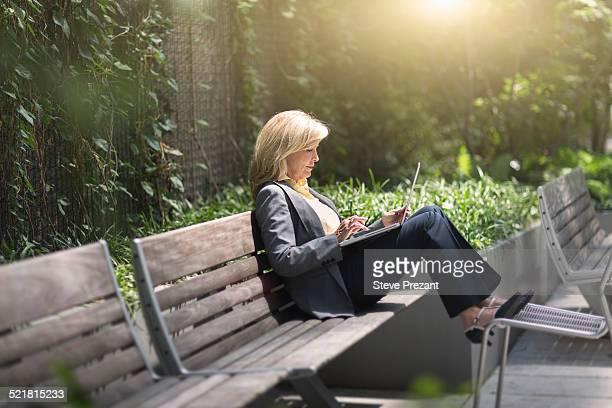 Mature businesswoman sitting on bench using laptop