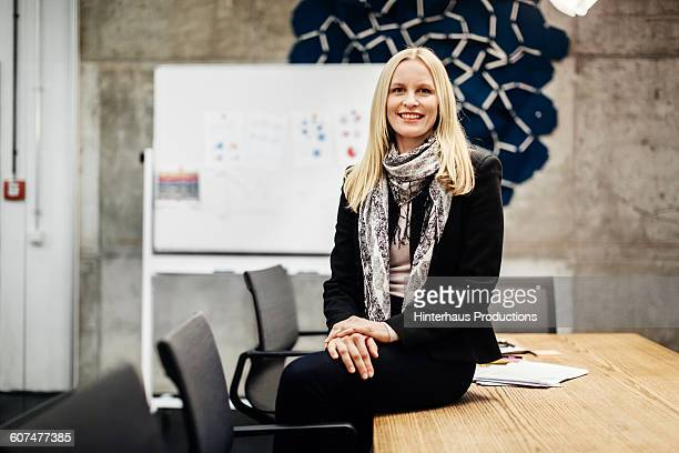 Mature businesswoman sitting on conference table