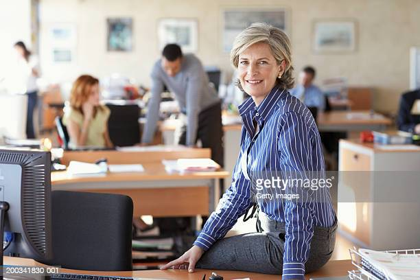 Mature businesswoman sitting on desk in office, smiling, portrait