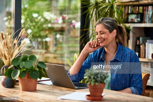 mature businesswoman smiling and listening on video conference - greater london stock pictures, royalty-free photos & images