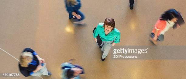 Reife Geschäftsfrau Lächeln und Blick nach oben in beschäftigt Büro-lobby