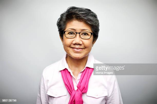 mature businesswoman smiling on white background - chinese culture stock pictures, royalty-free photos & images