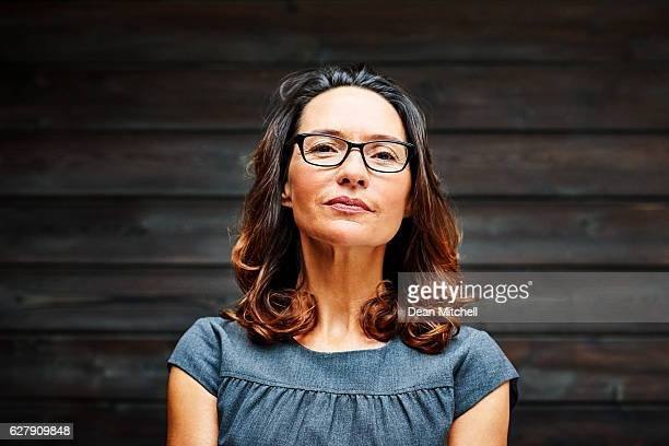 Mature businesswoman standing against a wooden wall in office