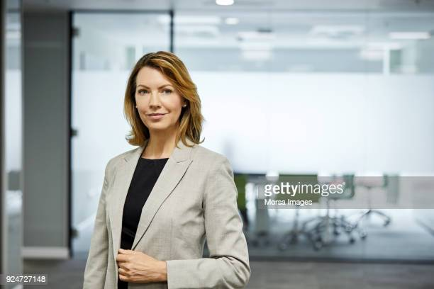Mature businesswoman standing against board room