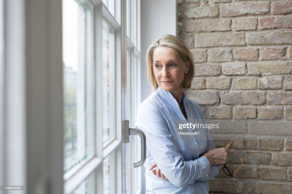 Mature businesswoman standing at window, looking worried : Stockfoto