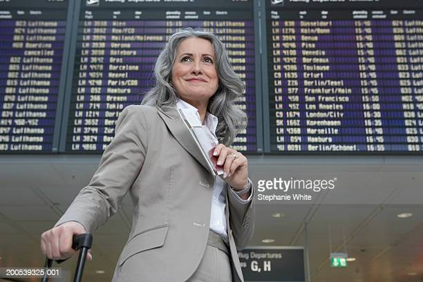 Mature businesswoman standing in airport, smiling, low angle view
