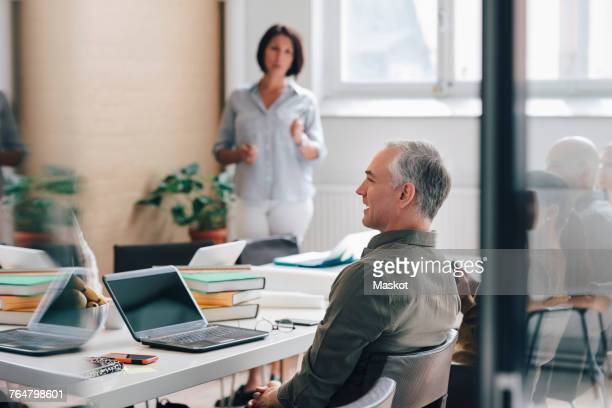 Mature businesswoman standing in board room with colleagues sitting at conference table