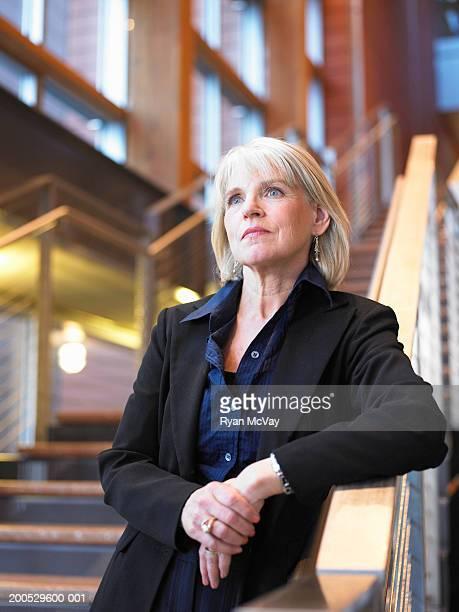 mature businesswoman standing on stairway, looking away - alleen één oudere vrouw stockfoto's en -beelden