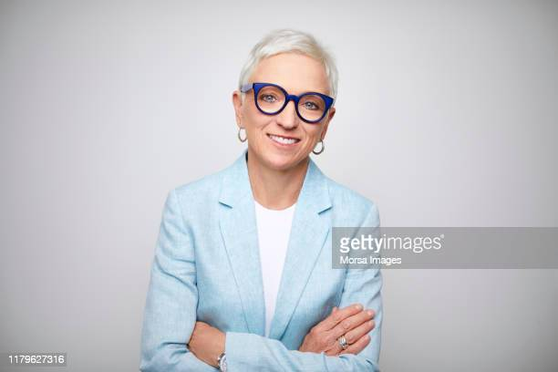 mature businesswoman standing with arms crossed - design professional stock pictures, royalty-free photos & images