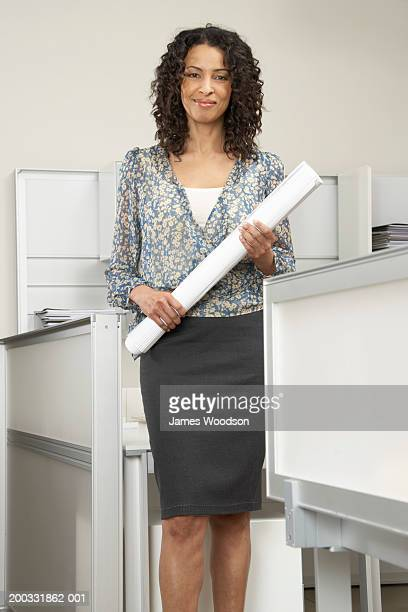 Mature businesswoman standing with scroll in office, smiling, portrait