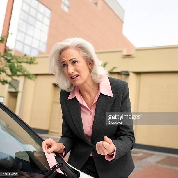Mature businesswoman taking out parking ticket put under wiper