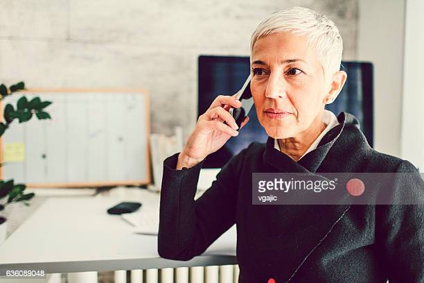 Mature Businesswoman Talking On The Phone In Her Home Office.
