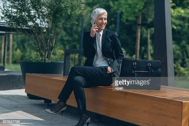 Ältere Geschäftsfrau reden am Telefon im Freien