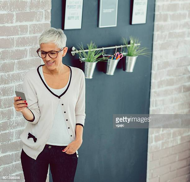 Mature Businesswoman Texting On Her Smart Phone