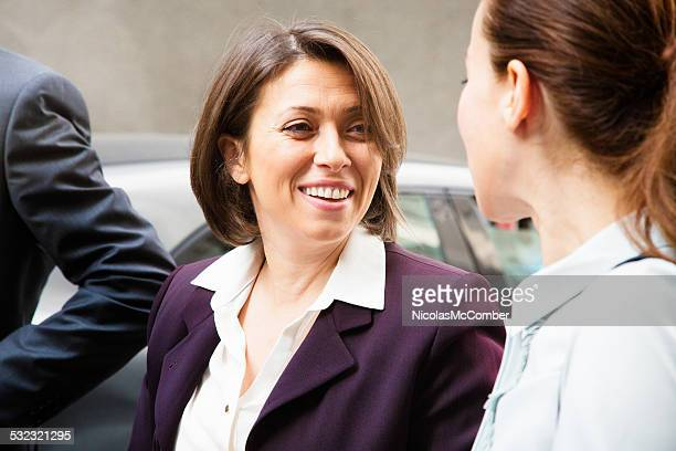 Mature businesswoman turns and smiles to her younger colleague