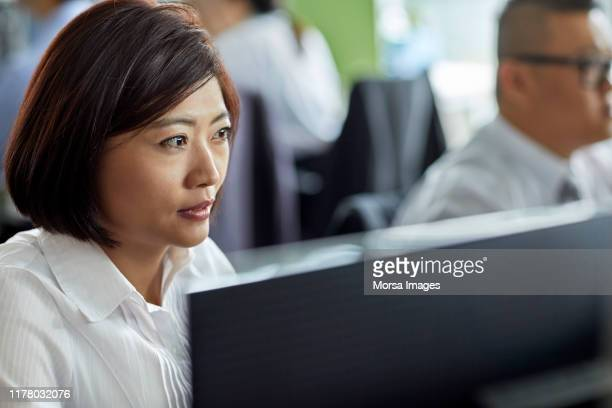 mature businesswoman using computer in office - short hair stock pictures, royalty-free photos & images