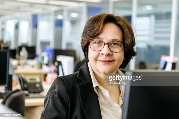 mujer de empresa madura usando computadora en la oficina - 55 59 años fotografías e imágenes de stock