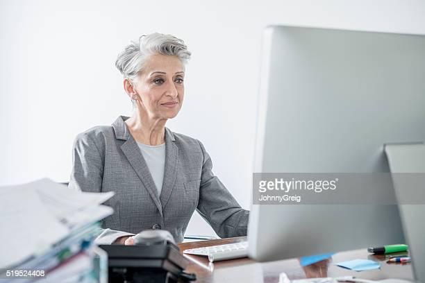 Reife Geschäftsfrau mit desktop-computer, Konzentration