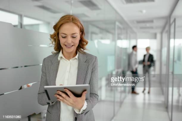 mulher de negócios madura que usa a tabuleta digital no corredor do edifício de escritórios - figurantes incidentais - fotografias e filmes do acervo