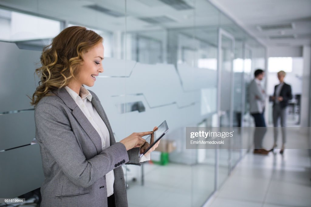 Mature businesswoman using digital tablet in office building hallway : Stock Photo