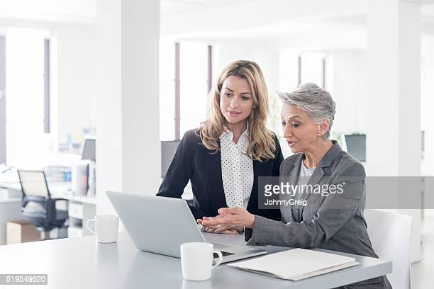 Mature businesswoman using latop with younger female colleague