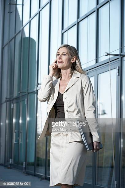 Mature businesswoman using mobile phone outside office building